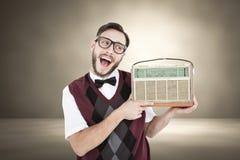 Sammansatt bild av den geeky hipsteren som rymmer en retro radio Royaltyfri Bild