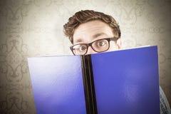 Sammansatt bild av den geeky studenten som läser en bok Royaltyfria Bilder