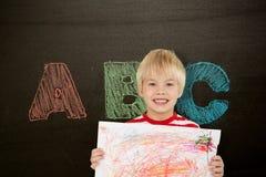 Sammansatt bild av den gulliga pojken som visar hans konst Royaltyfria Foton