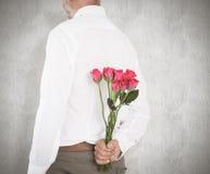 Sammansatt bild av den hållande buketten för man av rosor bak baksida Royaltyfria Bilder