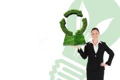 Sammansatt bild av den hållande gräsmattaboken för kvinna Arkivfoto