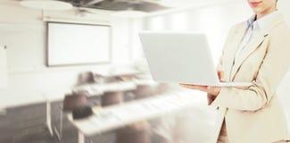 Sammansatt bild av den hållande bärbara datorn för säker affärskvinna Arkivbilder
