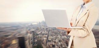 Sammansatt bild av den hållande bärbara datorn för säker affärskvinna Arkivfoto
