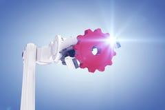 Sammansatt bild av den kantjusterade bilden av den robotic handen som rymmer det röda kugghjulet 3d Arkivbild
