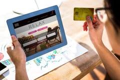 Sammansatt bild av den kantjusterade bilden av hipsteraffärsmannen som använder minnestavlan och kreditkorten Royaltyfri Foto