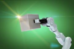Sammansatt bild av den kantjusterade bilden av robothanden som rymmer den metalliska kuben 3d Royaltyfri Foto