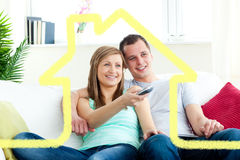 Sammansatt bild av den karismatiska mannen som omfamnar hans flickvän, medan hålla ögonen på tv Arkivfoton