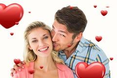 Sammansatt bild av den kyssande flickvännen för stilig man på kind Royaltyfria Bilder