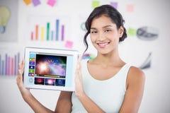Sammansatt bild av den lyckliga affärskvinnan som visar den digitala minnestavlan i idérikt kontor Arkivbilder