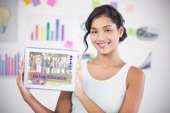 Sammansatt bild av den lyckliga affärskvinnan som visar den digitala minnestavlan i idérikt kontor Royaltyfri Fotografi