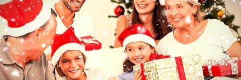 Sammansatt bild av den lyckliga familjen på jul som byter gåvor royaltyfri bild