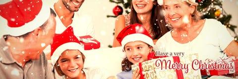 Sammansatt bild av den lyckliga familjen på jul som byter gåvor fotografering för bildbyråer