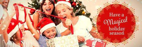 Sammansatt bild av den lyckliga familjen på jul som tillsammans öppnar gåvor royaltyfria foton