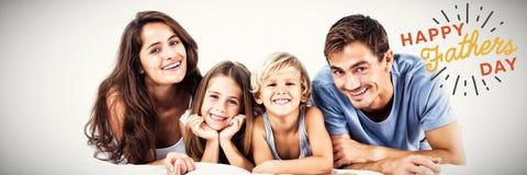 Sammansatt bild av den lyckliga familjen som ligger på en säng royaltyfri fotografi