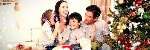 Sammansatt bild av den lyckliga familjen som spelar med julgåvor fotografering för bildbyråer