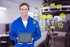 Sammansatt bild av den lyckliga mekanikern som rymmer den digitala minnestavlan Royaltyfria Foton