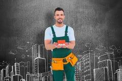 Sammansatt bild av den lyckliga modellen för byggnadsarbetareinnehavhus Royaltyfri Bild