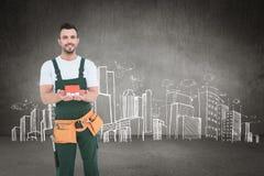 Sammansatt bild av den lyckliga modellen för byggnadsarbetareinnehavhus Royaltyfria Bilder