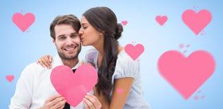 Sammansatt bild av den nätta brunetten som ger pojkvän en kyss och hennes hjärta Arkivfoto