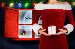 Sammansatt bild av den nätta flickan i hållande gåva för santa dräkt Royaltyfria Foton