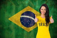 Sammansatt bild av den nätta fotbollsfan i den Brasilien tshirten Royaltyfri Bild