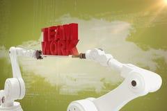 Sammansatt bild av den robotic handen som rymmer röd lagarbetstext över vit bakgrund Arkivbilder