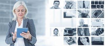 Sammansatt bild av den säkra affärskvinnan som använder den digitala minnestavlan royaltyfri foto