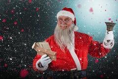 Sammansatt bild av den Santa Claus det hållande kuvertet och klockan Arkivfoto