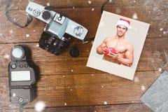 Sammansatt bild av den shirtless macho mannen i hållande gåva för santa hatt royaltyfria bilder