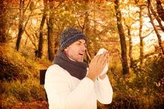 Sammansatt bild av den sjuka mannen, i att nysa för vintermode Arkivfoton
