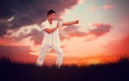 Sammansatt bild av den stiliga mannen i den vita görande tai-chien Arkivbild