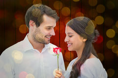 Sammansatt bild av den stiliga mannen som erbjuder hans flickvän en ros Royaltyfri Foto
