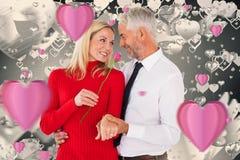 Sammansatt bild av den stiliga mannen som ger hans fru en rosa färgros Royaltyfri Bild