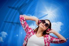 Sammansatt bild av den tillfälliga brunetten som lyssnar till musik Royaltyfri Foto