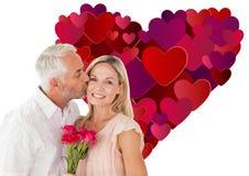 Sammansatt bild av den tillgivna mannen som kysser hans fru på kinden med rosor Royaltyfria Bilder