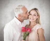 Sammansatt bild av den tillgivna mannen som kysser hans fru på kinden med rosor Royaltyfri Fotografi