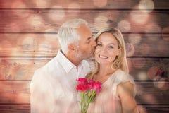 Sammansatt bild av den tillgivna mannen som kysser hans fru på kinden med rosor Arkivbild