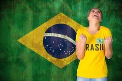 Sammansatt bild av den upphetsade fotbollsfan i den Brasilien tshirten Arkivfoton