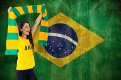 Sammansatt bild av den upphetsade fotbollsfan i den Brasilien tshirten Royaltyfria Bilder