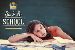 Sammansatt bild av den uttråkade kvinnliga studenten som gör hennes läxa Royaltyfri Fotografi