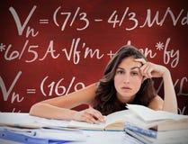 Sammansatt bild av den uttråkade studenten som gör hennes läxa Royaltyfria Foton