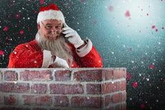 Sammansatt bild av det Santa Claus anseendet bredvid lampglaset och samtal på mobiltelefonen Royaltyfri Bild