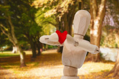 Sammansatt bild av det träanseendet och innehavet för statyett 3d en röd hjärta framme Royaltyfri Fotografi