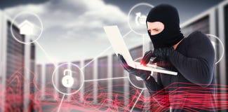 Sammansatt bild av en hacker som använder bärbara datorn för att stjäla identitet royaltyfria foton