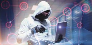 Sammansatt bild av en hacker som använder bärbara datorn för att stjäla identitet arkivbild