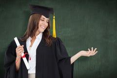 Sammansatt bild av en kvinna som ut rymmer hennes hand med en grad i hennes annan hand, som hon ler Royaltyfri Bild
