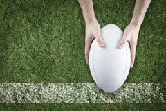 Sammansatt bild av en rugbyspelare som poserar en rugbyboll Fotografering för Bildbyråer
