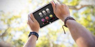 Sammansatt bild av enarmade banditen med symboler på den mobila skärmen Royaltyfria Foton