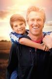 Sammansatt bild av fadern som bär hans son på hans skuldror royaltyfri foto