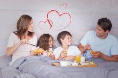 Sammansatt bild av familjen som har frukosten i säng Arkivbild
